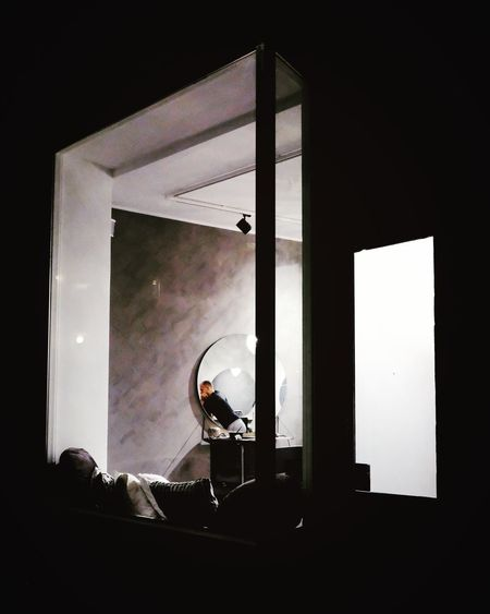 Side view of man sitting on window at home