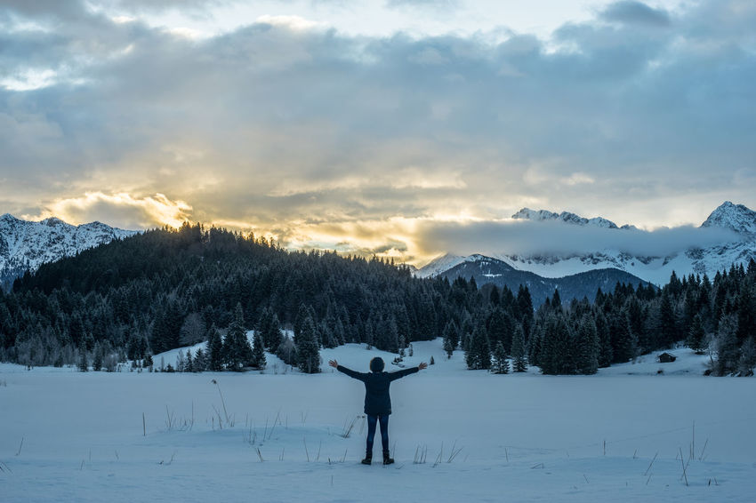 Arms Raised Beauty In Nature Cloud - Sky Cold Temperature Field Human Arm Leisure Activity Lifestyles Limb Mountain Nature Non-urban Scene One Person Outdoors Plant Real People Scenics - Nature Sky Snow Standing Tree Warm Clothing Winter