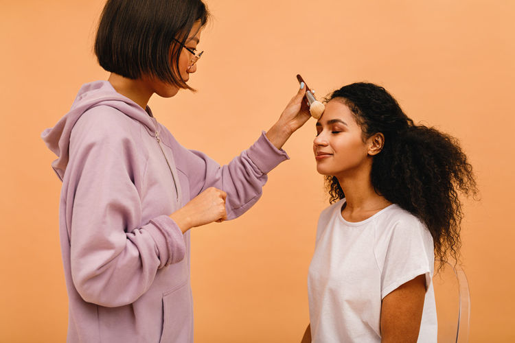 Woman doing make-up of woman against orange background