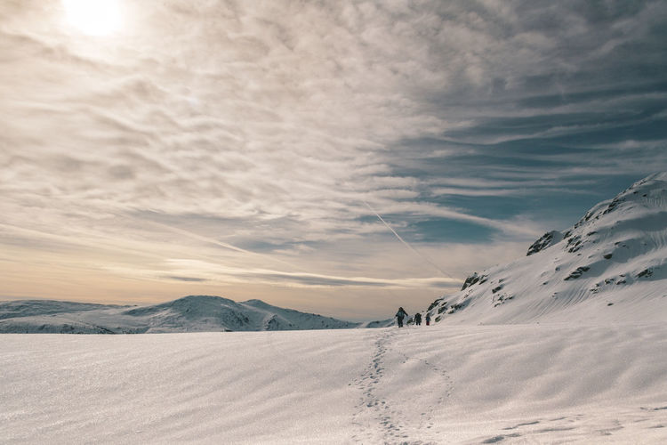 Scenic view of snowy landscape against cloudy sky during winter
