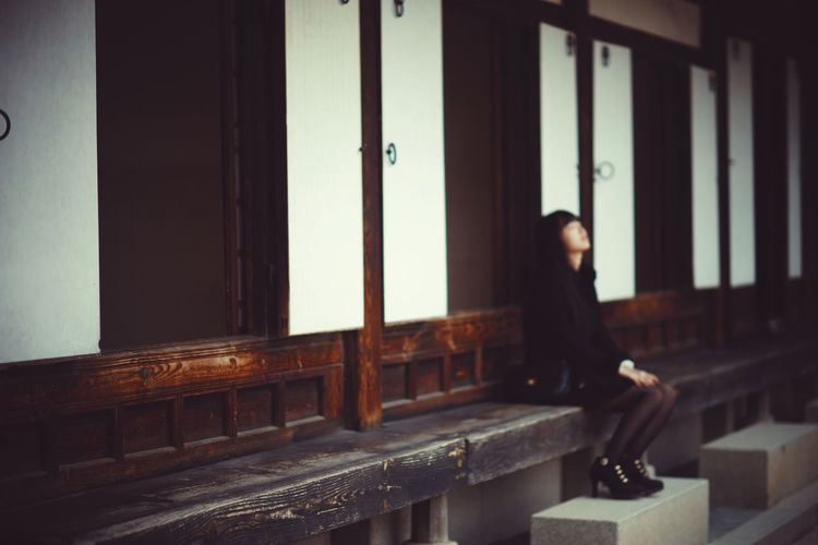 Full Length Of Depressed Woman Sitting By House