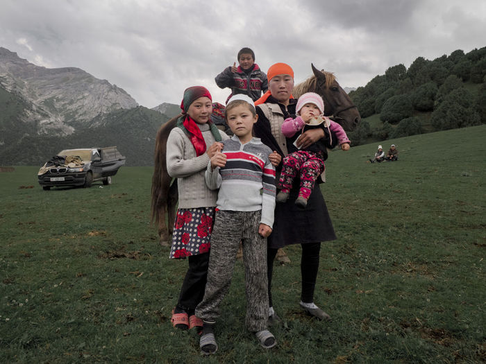 A Kyrgyz family from the village in Kyrgyz Ata in the Alay mountains in Kyrgyzstan Kyrgyz Kyrgyzstan Travel Travel Photography Child Childhood Family Females Group Of People Looking At Camera Mountain Nomadic Sky Standing Togetherness The Photojournalist - 2018 EyeEm Awards The Traveler - 2018 EyeEm Awards The Portraitist - 2018 EyeEm Awards