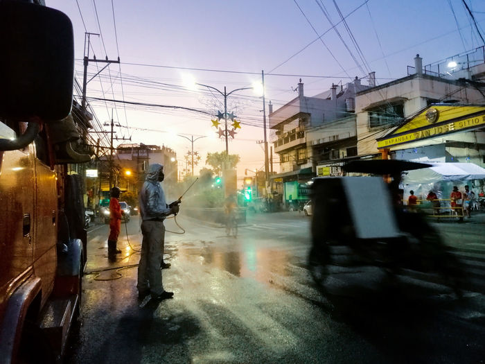 People walking on wet city street during rainy season