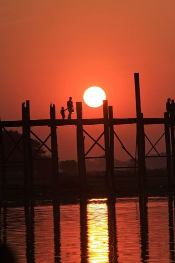 Silhouette man and child on u bein bridge over river during sunset