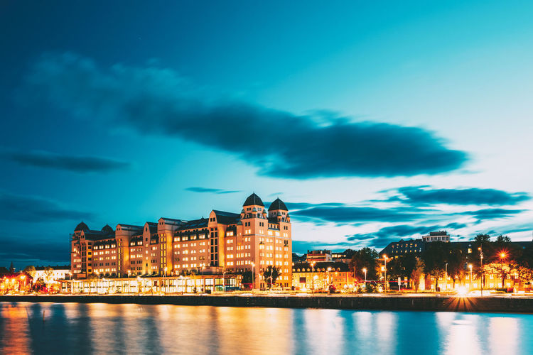 Evening view of the house on the citys waterfront, illuminated by night lights in Oslo, Norway. Architecture Water Sky City Night Waterfront Reflection River Cityscape Building Blue Light Clouds Evening Illuminated Oslo Norway View Modern Town Yellow