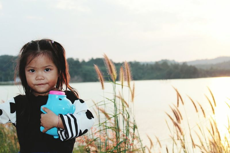 Portrait Of Girl Standing With Piggy Bank Against Clear Sky