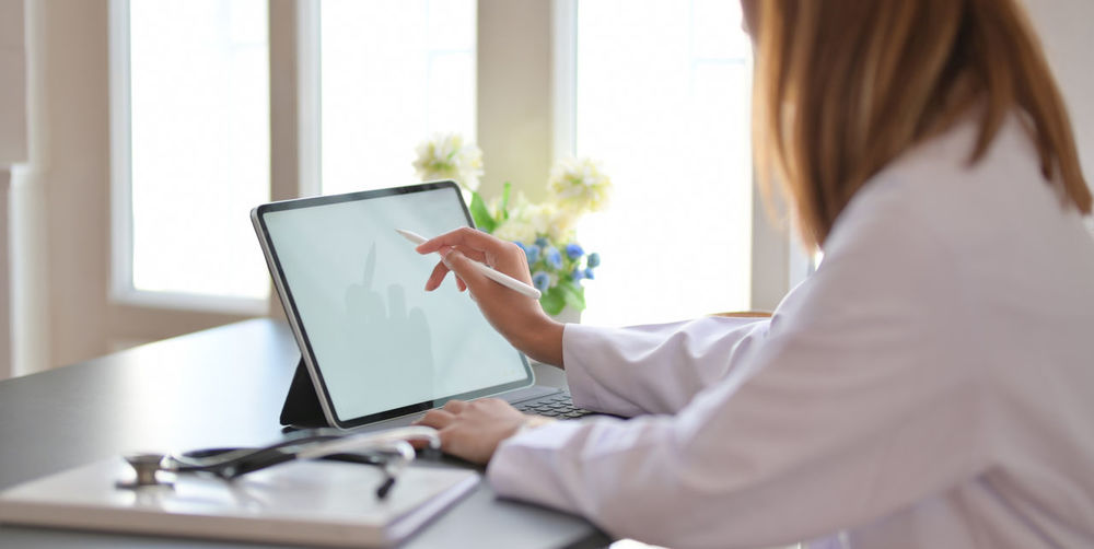 Midsection of doctor using digital tablet in clinic
