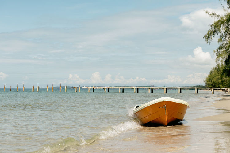Boat on the Beach Sea Nature Scenics - Nature Beauty In Nature Beach No People Boat Sandy Beach Summer Summertime Summery Hot Day Holiday Vacations Travel Tourism Beautiful Pier Shore Hot Weather Paradise Tranquil Scene Outdoors Nature Waterfront