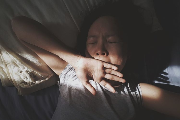 High angle view of woman yawning while lying on bed at home