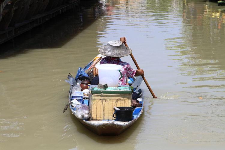 Rear view of market vendor in river