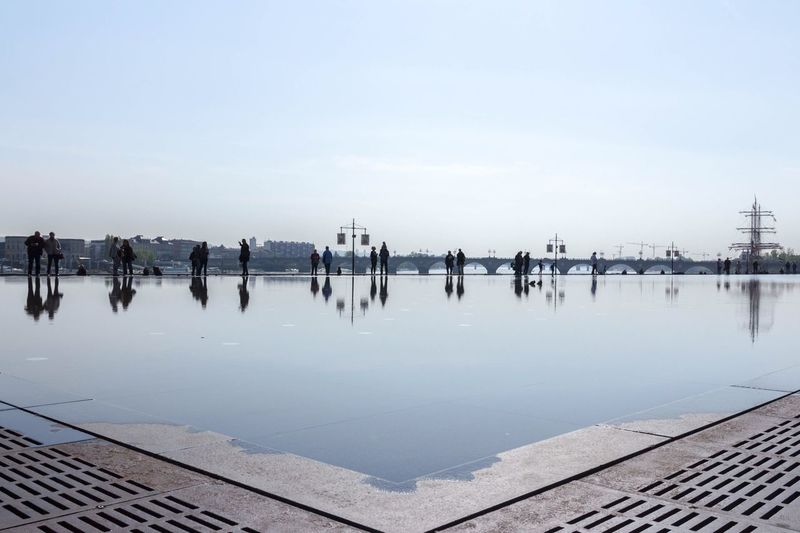 People reflecting in water while standing against sky
