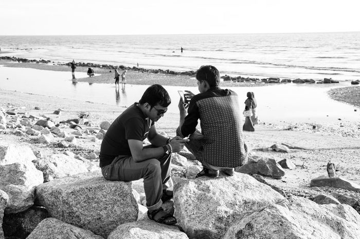 Internet Addiction Togetherness Beach Sea Shore Sitting People Black And White Leisure Activity Non-urban Scene Non Urban Scene People Photography Casual Clothing Outdoors Street Photography Streetphotography People And Places