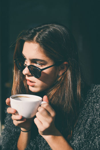 Close-up of woman drinking coffee in sunglasses