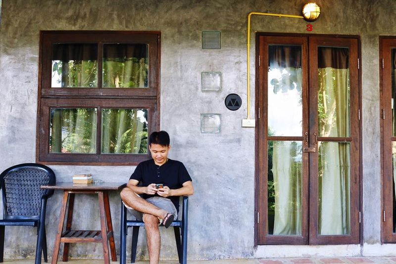 Man using phone while sitting on chair outside house