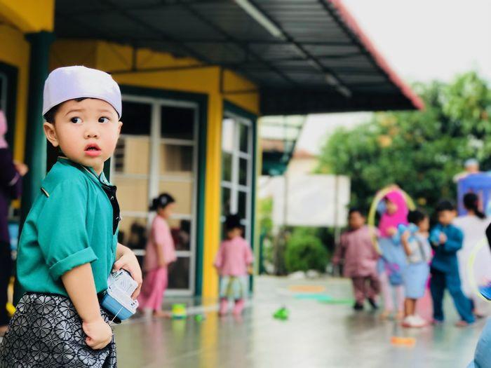 Cute boy standing against school
