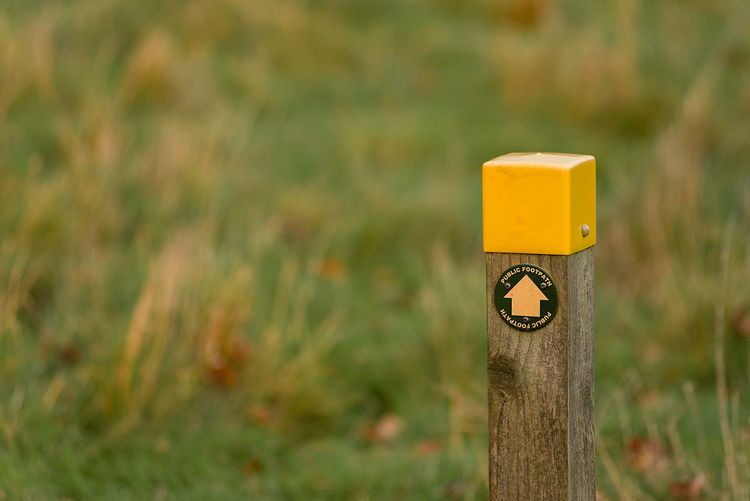 A wooden public footpath sign post leading in to an autumn grassy field. Arrow Directional Sign Footpath Grass Path Post Sign Close-up Day Focus On Foreground Grass Nature No People Outdoors Public Footpath Wooden Post Yellow