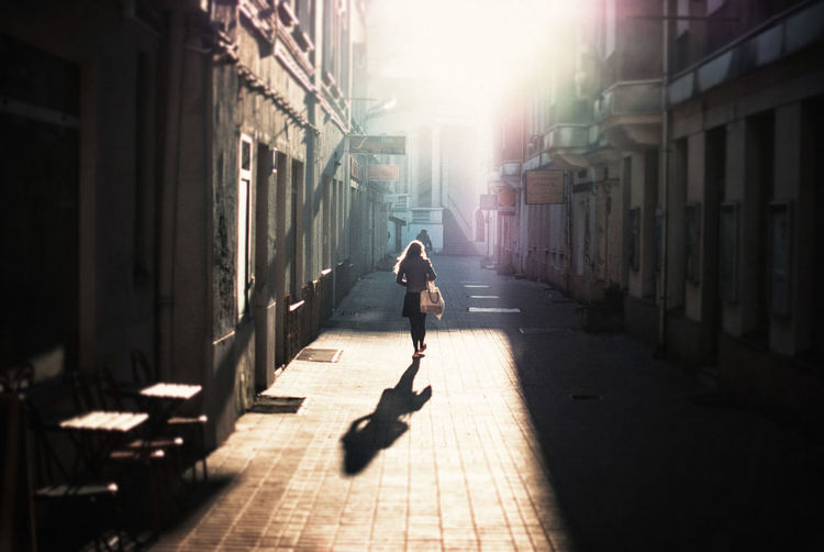 Rear view of woman walking on alley during sunny day