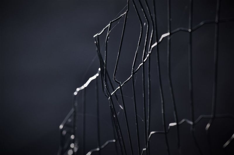 Close-up of metal fence at night