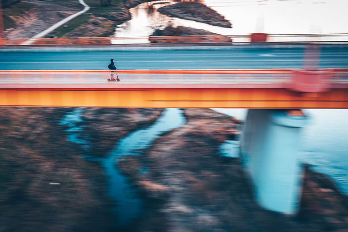 Blurred motion of person riding push scooter on bridge