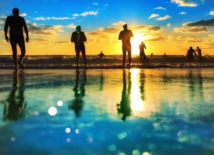 Reflection of men on water in city