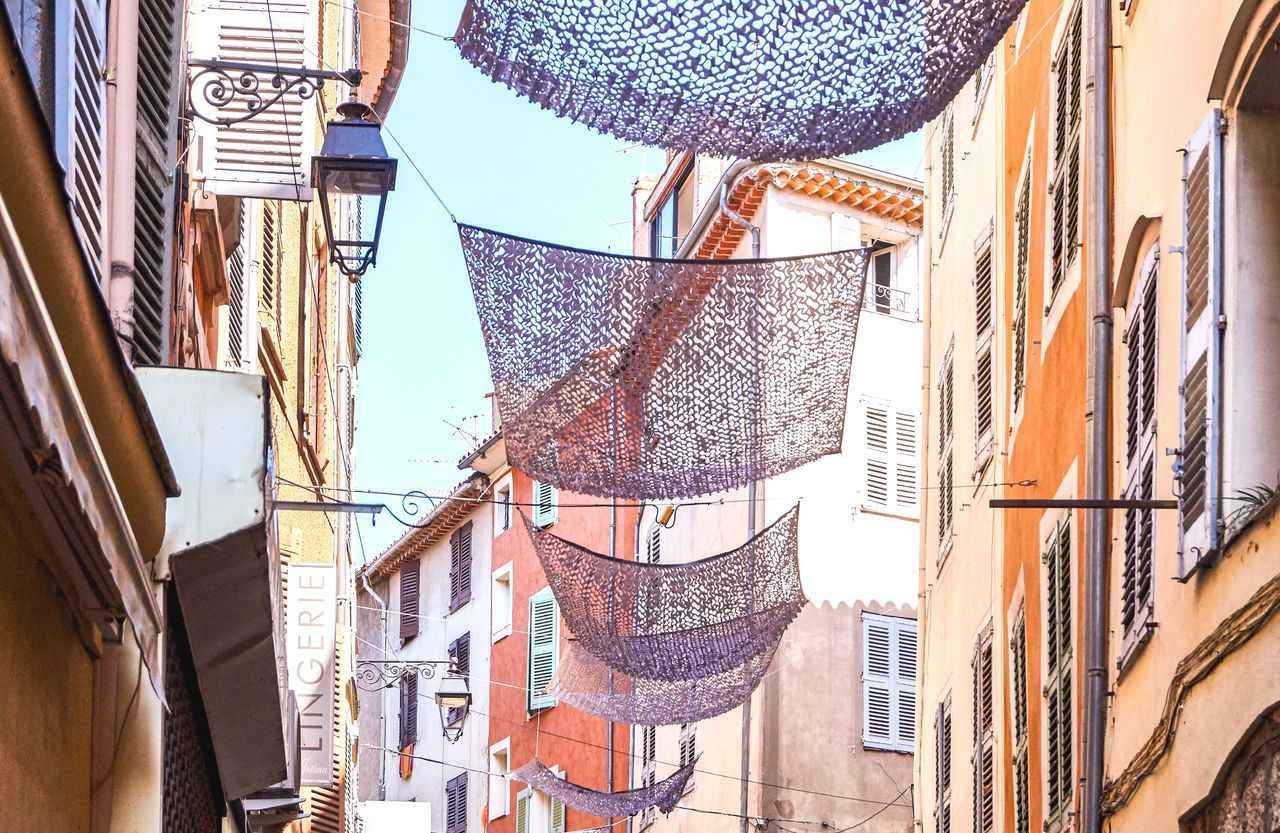 building exterior, built structure, architecture, hanging, low angle view, day, building, no people, clothing, residential district, textile, window, city, outdoors, drying, wall - building feature, nature, curtain, laundry, sunlight