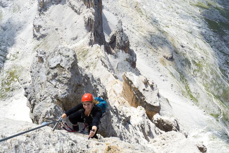 High angle portrait of woman climbing on rock