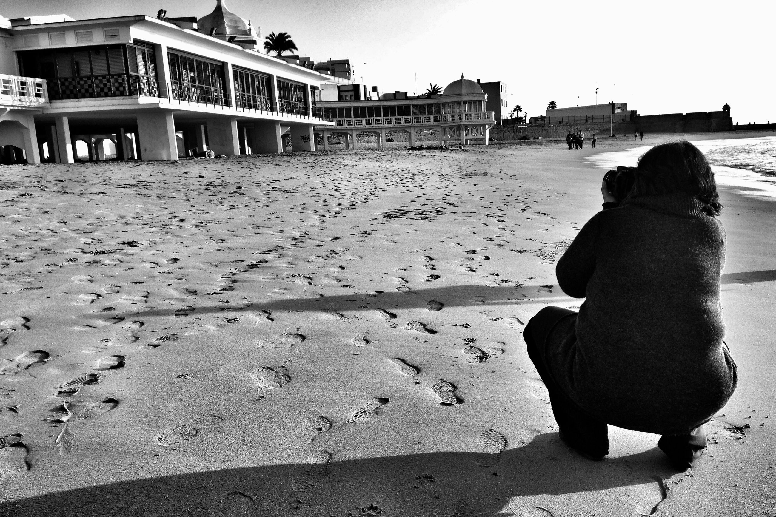 beach, lifestyles, architecture, leisure activity, built structure, sea, building exterior, sand, person, shore, rear view, men, sky, water, sunlight, shadow, standing, relaxation