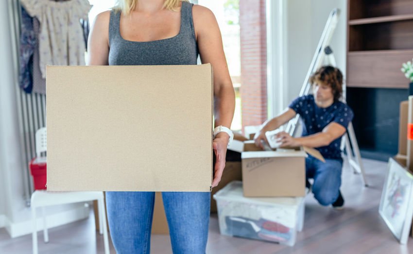 Woman carrying moving box while her husband unpacks Box Cardboard Box Couple Family Happy Horizontal Man Moving New Unpacking Woman Apartment Cardboard Caucasian Enjoy Female Holding House Lifestyles Male Mortgage Packed Real People Relocation Smiling