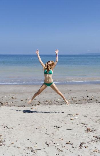 Woman in bikini jumping at shore against clear sky
