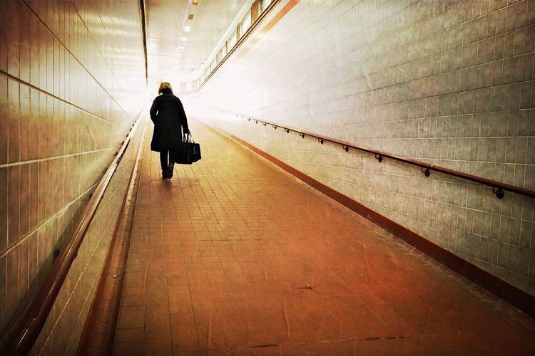 Rear view of a woman walking in subway