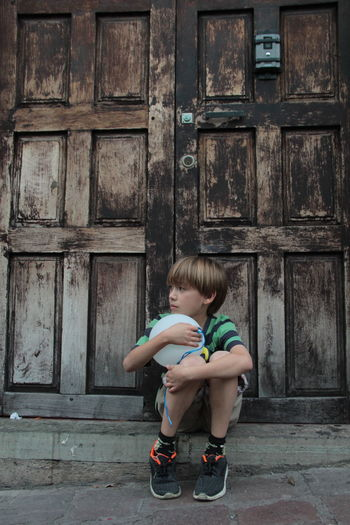 child with a globe in a sad moment Awaiting Children Sadness And Sorrow Building Exterior Child Childhood Children Photography Day Full Length Globe Lifestyles One Person Outdoors People Real People Sad Sad & Lonely Sad Face Sadness