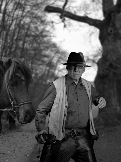 Portrait of man with horse at forest against sky