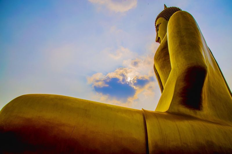 Low angle view of giant buddha statue against sky