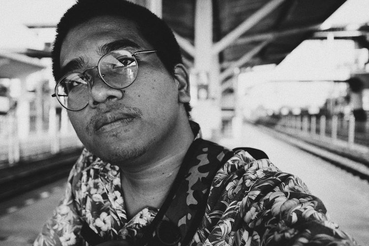 Portrait of man wearing eyeglasses at railroad station