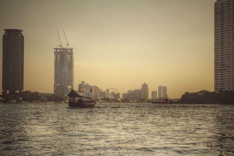 Sea by buildings against clear sky
