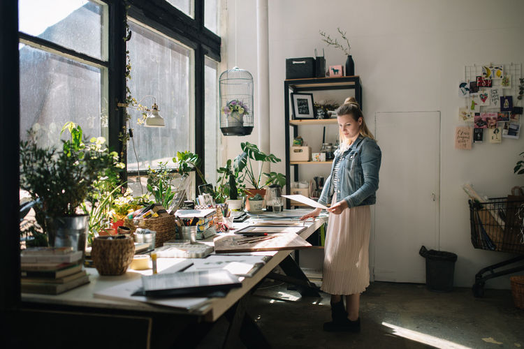 Woman Working At Desk In Workshop