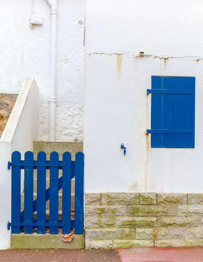 Closed blue door and window on wall of building