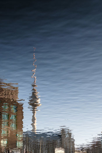 Reflection of building in water against sky