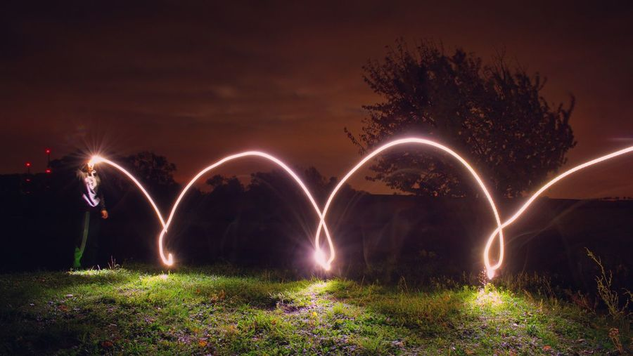 Light painting on field against sky at night