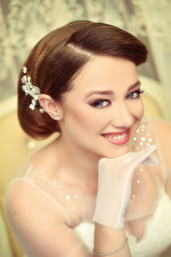 Close-Up Portrait Of Happy Beautiful Bride With Hand On Chin At Home