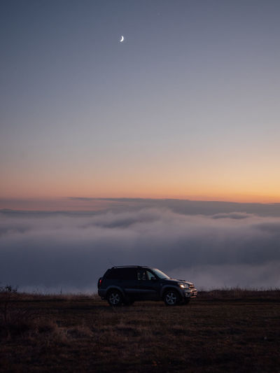 Car on land against sky during sunset