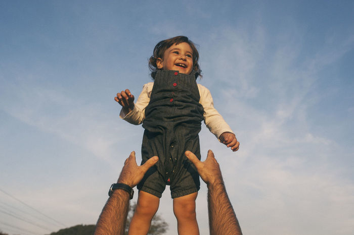 Cropped hands of father reaching daughter against sky