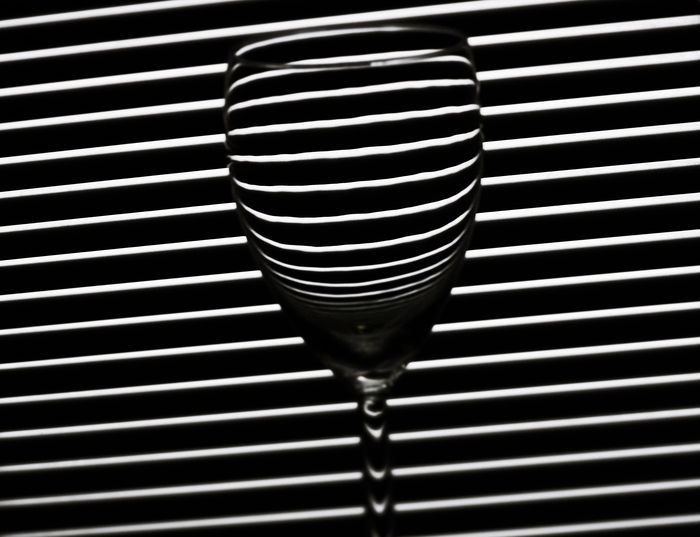 Single wine glass, backlit. Black & White Geometric Shapes Wine Glass Abstract Backlit Close-up Drink Drinking Empty Glass Focus On Foreground Food And Drink Household Equipment Illusion Indoors  Kitchen Art Lines, Shapes And Curves Monochrome No People Pattern Refraction Single Object Still Life Striped