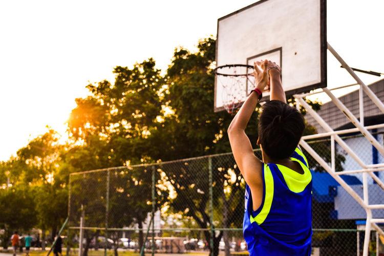 Man reaching basketball hoop against sky