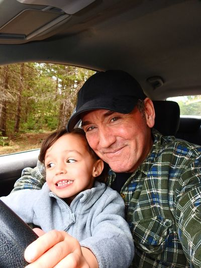 Portrait of smiling man with granddaughter sitting in car