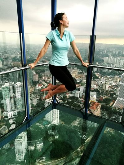Woman Balancing On Railing Over Glass Floor At Menara Kuala Lumpur Tower