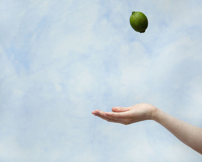 Cropped Hand Catching Lime Against Cloudy Sky