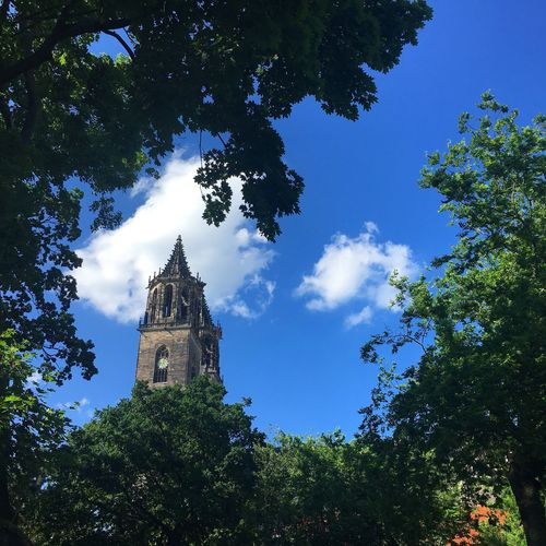 Sky Building Exterior Blue Clock Tower Tree Religion Beauty In Nature Low Angle View Architecture Day Built Structure Cloud - Sky History No People Outdoors Growth Place Of Worship Travel Destinations Nature Bell Tower First Eyeem Photo