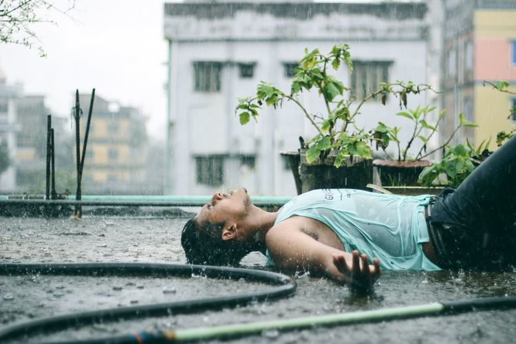Young man lying on street in city during rainy season