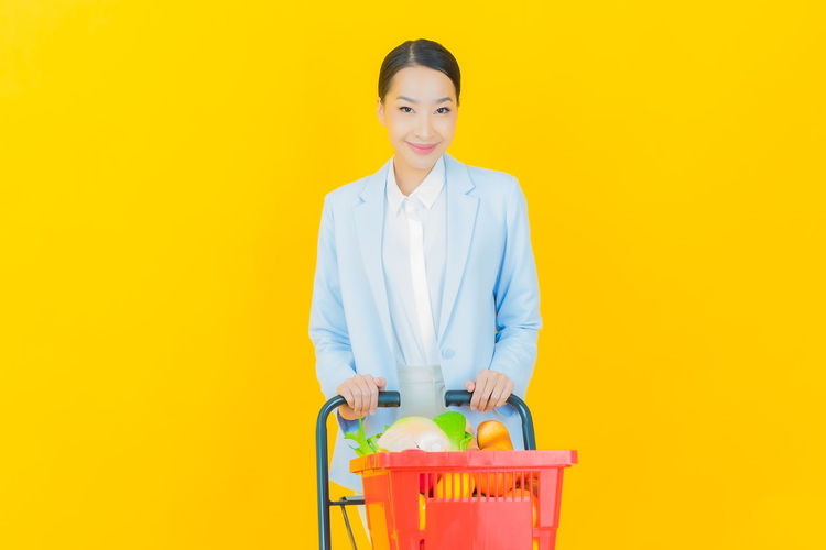 Portrait of smiling woman standing against yellow background